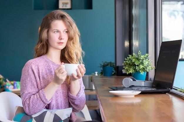 Dziewczyna pracuje na laptopie. praca zdalna, online. dziewczyna w kawiarni przy filiżance kawy