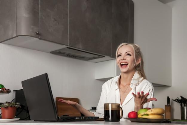Dziewczyna pracuje na laptopie w kuchni w domu i bardzo emocjonalna. kobieta gesty rękami.