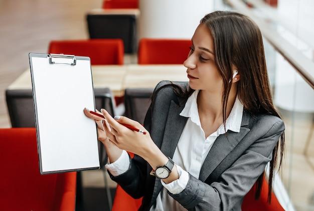 Dziewczyna pracuje na laptopie w miejscu pracy. kobieta pokazuje i wyjaśnia cele i zadania dla firmy. kobieta sukcesu tworzy startup i podejmuje decyzje.