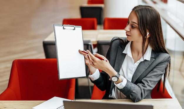 Dziewczyna pracuje na laptopie w miejscu pracy. kobieta pokazuje i wyjaśnia cele i zadania dla firmy.