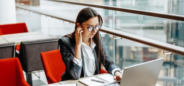 Dziewczyna pracuje na laptopie w miejscu pracy. kobieta sukcesu w biznesie tworzy startup i podejmuje decyzje.