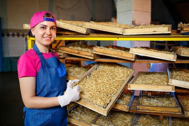 Dziewczyna pracuje nad produkcją spaghetti. robienie makaronu. fabryka makaronów.