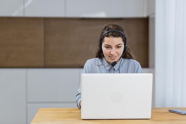 Dziewczyna pracuje online z laptopem za pomocą zestawu słuchawkowego