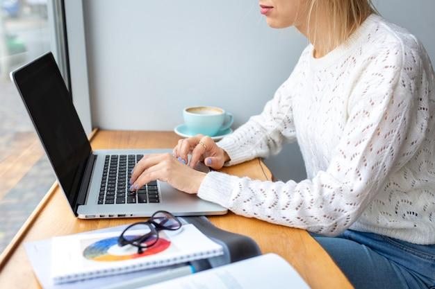 Dziewczyna pracuje przy laptopie przy filiżance kawy. praca w domu. czas na siebie.
