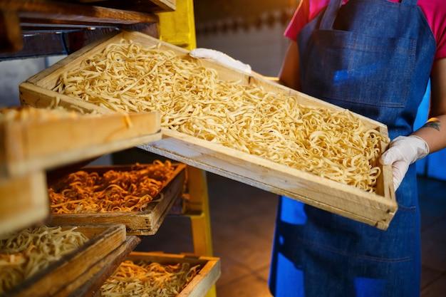 Dziewczyna pracuje przy produkcji spaghetti. robienie makaronu. fabryka makaronów. produkcja etapowa makaronów. surowy makaron. pracownik z pudełkiem makaronu.