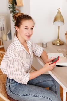 Dziewczyna pracuje w domu przez telefon