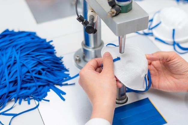 Dziewczyna pracuje w fabryce do produkcji masek medycznych z nanowłókien i pętli lutowniczych z ultradźwiękami na maszynie.