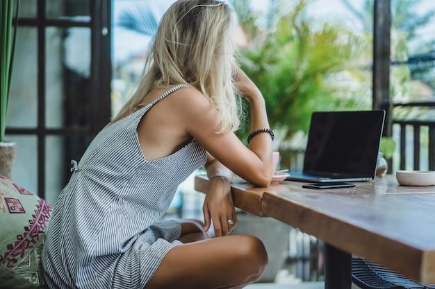Dziewczyna pracuje w kawiarni. koncepcja freelancing, kawa i laptop.