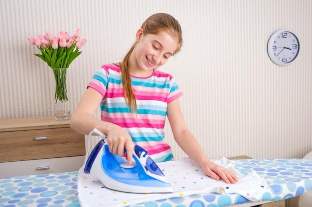 Dziewczyna prasowanie ubrań na pokładzie w domu