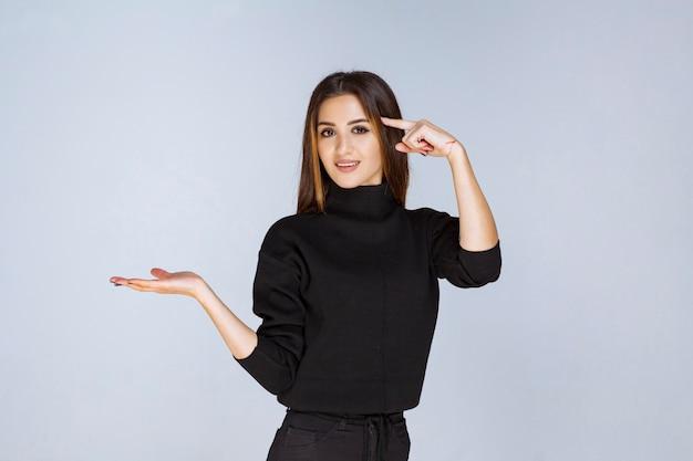 Dziewczyna prezentuje coś w jej otwartej dłoni. zdjęcie wysokiej jakości