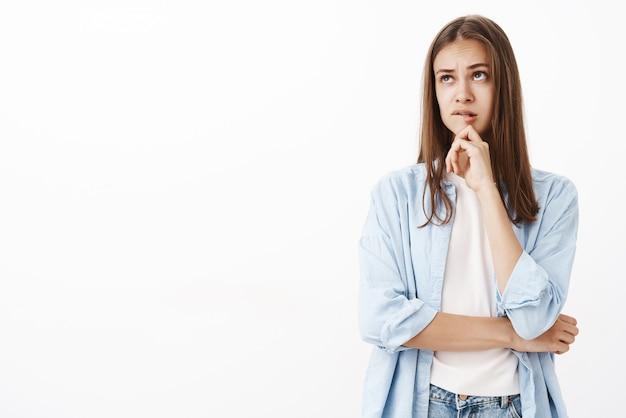 Dziewczyna próbująca nadrobić makijaż myśli tworzenie obrazu w umyśle stojąca zakłopotana i zamyślona gryząca dolną wargę, myśląca dotykając brody, patrząc w górę krzyżując ramię na klatce piersiowej
