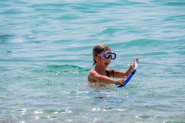 Dziewczyna próbuje nurkować pod wodą z zabawą w morzu. ludzie aktywni, sport wodny. lekcje pływania w wakacje letnie. gry wodne. copyspace