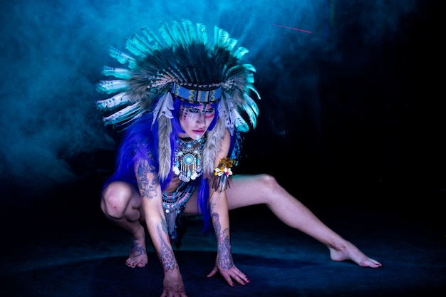 Dziewczyna przebrana za indiankę z piórami na głowie pozuje w ciemności do malowania światłem.