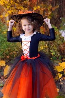 Dziewczyna przebrana za małą czarownicę w pomarańczową spódniczkę i spiczasty czarny kapelusz w jesiennym parku halloween
