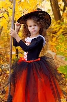 Dziewczyna przebrana za małą czarownicę w pomarańczowej spódnicy i spiczastym czarnym kapeluszu z miotłą w jesiennym parku halloween