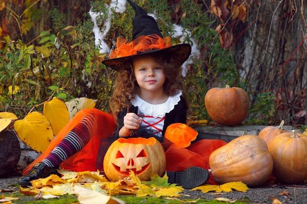 Dziewczyna przebrana za małą czarownicę w pomarańczowej spódniczce i spiczastym czarnym kapeluszu siedzi obok dyń na halloween w jesiennym parku