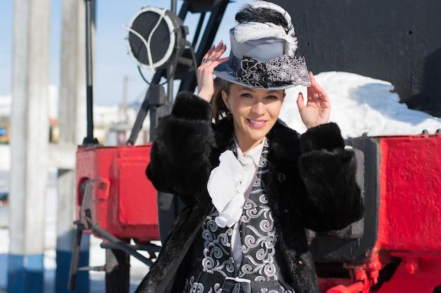 Dziewczyna przebrana za szlachciankę xix wieku przy lokomotywie parowej. rosyjska zima