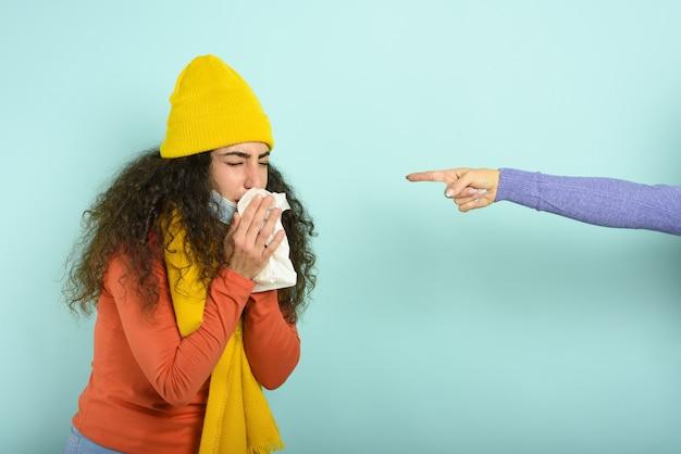 Dziewczyna przeziębiła się i ludzie myślą, że to wirus covid-19. niebieska ściana