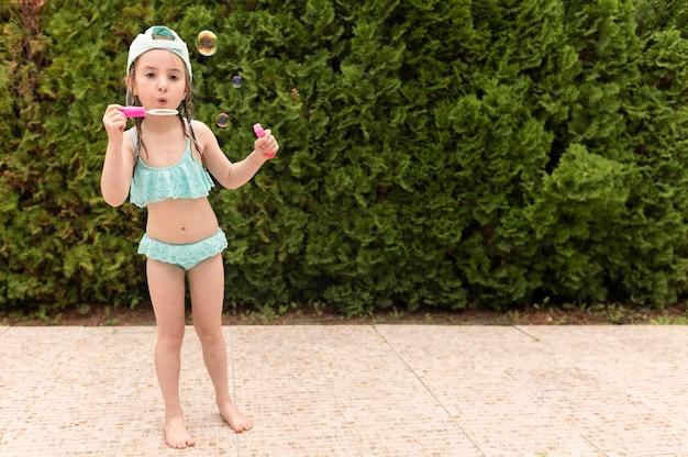 Dziewczyna przy basenem robi mydlanym bąblom