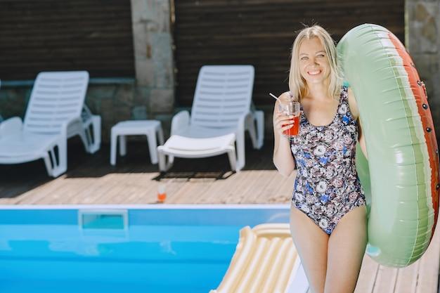 Dziewczyna przy basenie. kobieta w stylowych strojach kąpielowych. pani na wakacjach