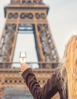 Dziewczyna przy lampce wina w pobliżu wieży eiffla w paryżu. selektywne ustawianie ostrości.