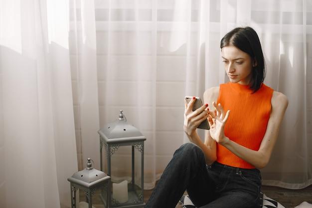 Dziewczyna przy oknie na podłodze przy użyciu telefonu komórkowego.