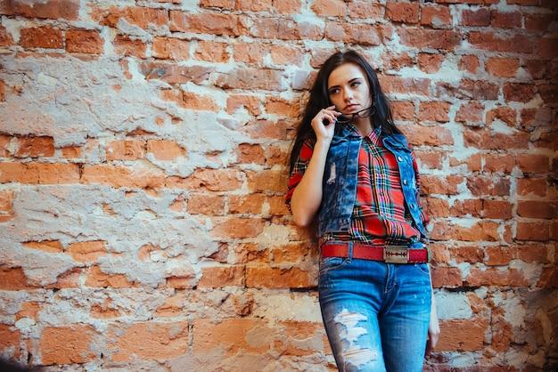 Dziewczyna przy ściana z cegieł. ciepłe kolory.