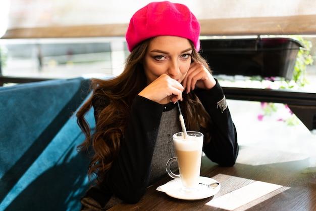 Dziewczyna przy stoliku w kawiarni pije kawę latte. w dowolnym celu.