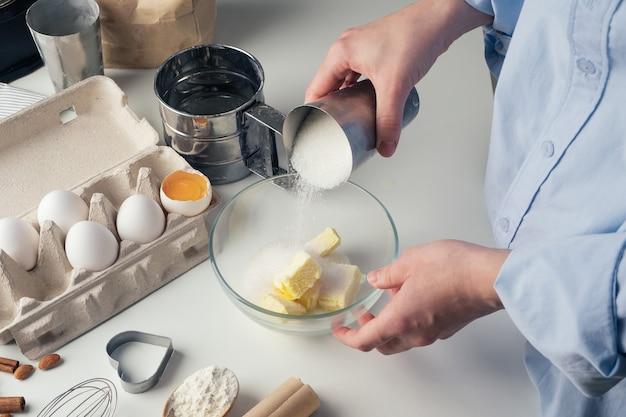 Dziewczyna przygotowuje ciasteczka w kuchni, wlewając cukier, zbliżenie.