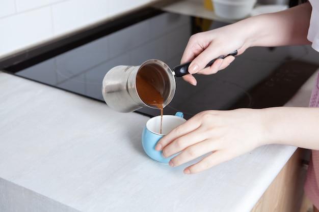 Dziewczyna przygotowuje kawę w kuchni