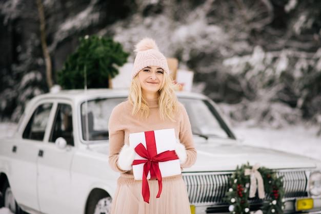 Dziewczyna przygotowuje się do bożego narodzenia, stoi z darem w ręce na tle retro samochodu, którego dach to choinka, prezenty i wieniec w zimowym śnieżnym lesie.