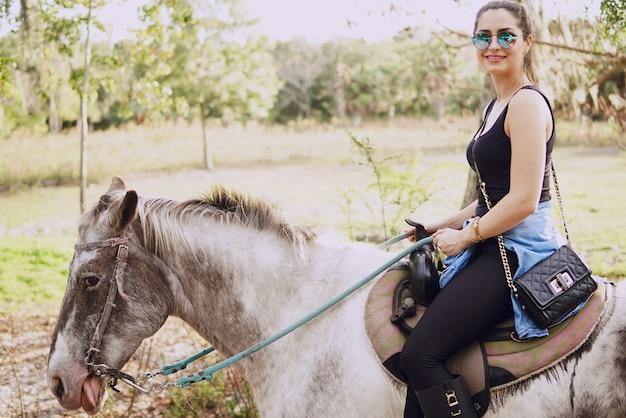 Dziewczyna przygotowuje się do jazdy koniem