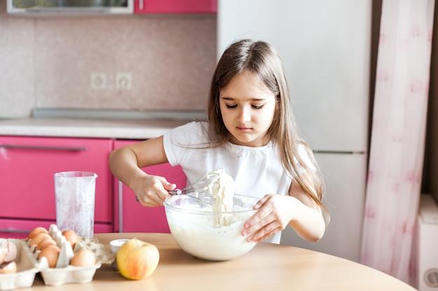 Dziewczyna przygotowuje śniadanie, pieczenie, zamieszać w misce mąki, mleka, jajek, naleśników, dzieci pomagają matce, śniadanie rodzinne, gotowanie