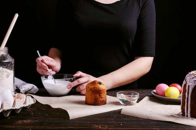 Dziewczyna przygotowuje wielkanocne wypieki, smaruje ciasto polewą i posypuje kolorowym proszkiem