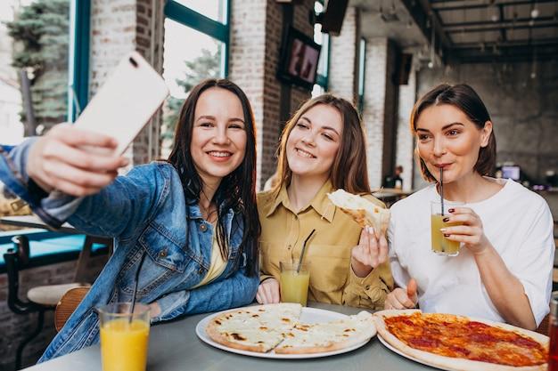 Dziewczyna przyjaciele ma pizzę przy barem przy lunchu czasem