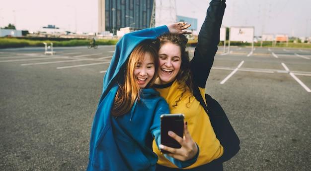 Dziewczyna przyjaciele uśmiecha się i biorąc selfie razem