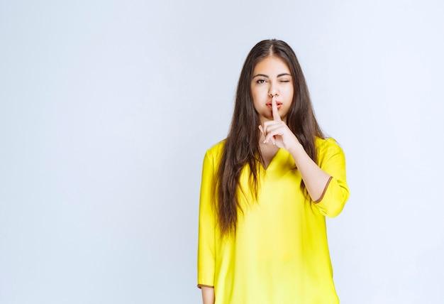Dziewczyna przykłada palec do ust i prosi o ciszę.