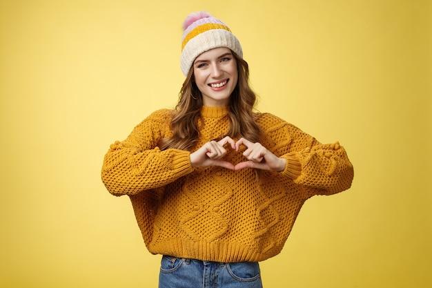 Dziewczyna przynosi pokój miłosny pokaz gest serca przechylanie głowy przyjazny uśmiech wyrażający współczucie pasja wyznanie chłopakowi ciepłe uczucia, znak złamanego serca, uśmiechający się zalotnie, stojący żółty tło