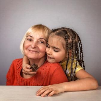 Dziewczyna przytula swoją babcię z miłością i z przyjemnością je tabliczki czekolady