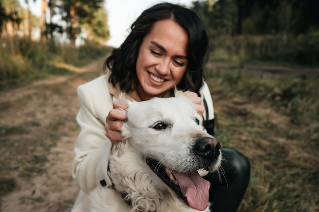 Dziewczyna przytulanie psa golden retriever w polu