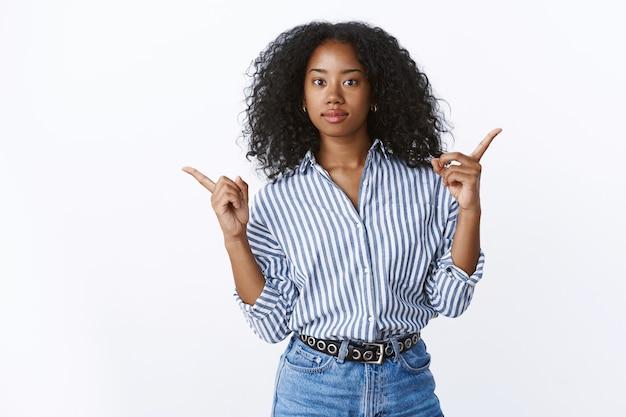 Dziewczyna pytająca o opinię jaki produkt kupić skierowana w bok obie lewa prawa konsultacja przed podjęciem decyzji, niepewna wybór niezdecydowana kamera zakwestionowana skomplikowany wybór, biała ściana