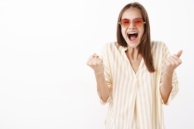 Dziewczyna radująca się z podniecenia i szczęścia zaciskająca pięści, krzycząca radośnie świętująca doskonałą wiadomość, stojąca zadowolona i rozbawiona w modnych okularach przeciwsłonecznych i bluzce