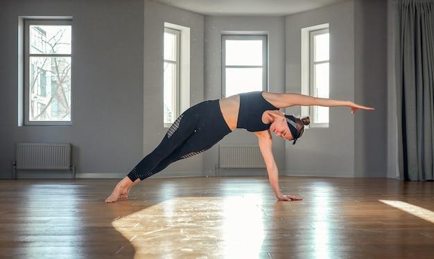 Dziewczyna rano jogi robi ćwiczenia rozciągające w sali do pilatesu.