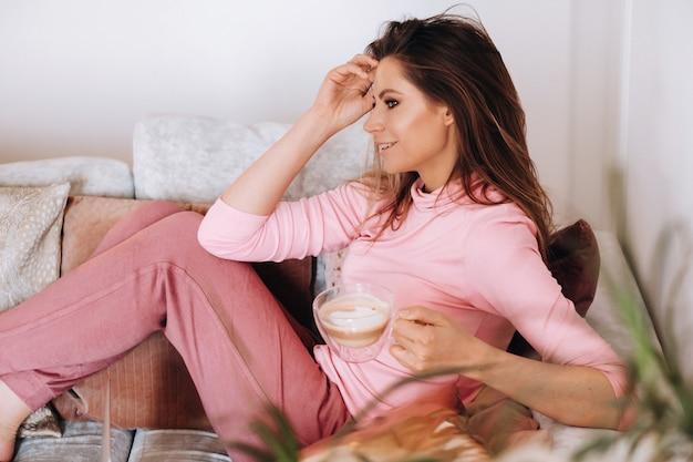 Dziewczyna rano w piżamie w domu, picie kawy