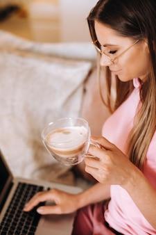 Dziewczyna rano w piżamie w domu pracuje na laptopie