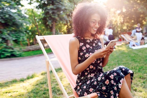 Dziewczyna rasy mieszanej siedzi na szezlongu na trawniku i wiadomości tekstowe na telefon komórkowy.