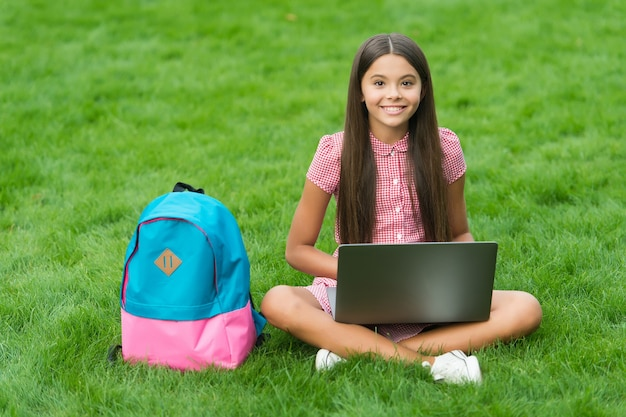 Dziewczyna reaguje podczas korzystania z laptopa siedzieć na zielonej trawie w parku z powrotem do szkoły, edukacja.