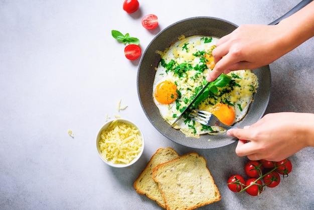 Dziewczyna ręce nad patelni z trzema gotowanymi jajkami, ziołami, serem, pomidorami