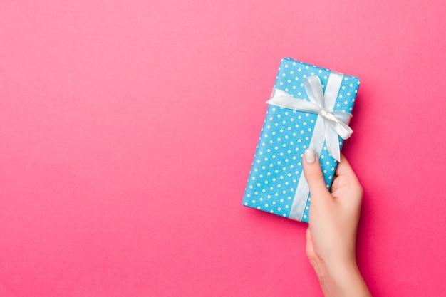 Dziewczyna ręce trzyma papierowe pudełko z prezentem na boże narodzenie lub inne święto na różowo
