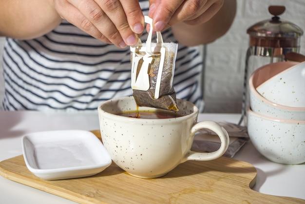 Dziewczyna ręce w ramce, zbliżenie, zrobić natychmiastową świeżo parzoną kawę z torby. modna odmiana dripa, w jasnej kuchni na stole z filiżankami, poranne słońce sun